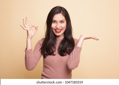 Beautiful young Asian woman show palm hand and OK sign on beige background
