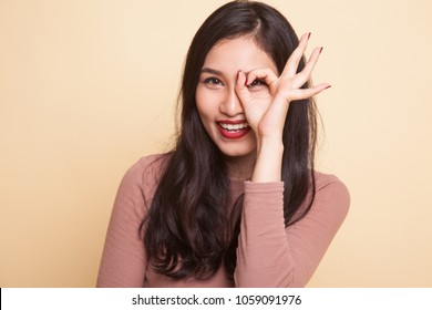 Beautiful young Asian woman show OK sign over her eye on beige background