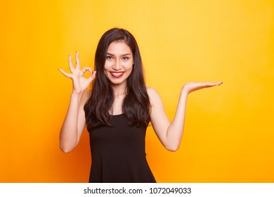 Beautiful young Asian woman show palm hand and OK sign on yellow background