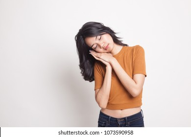 Beautiful young Asian woman with sleeping gesture on white background