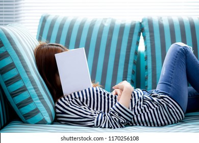Beautiful young asian woman sleeping on sofa with book covering her face because reading book with preparing exam of college, girl sleepy with tired so that leisure, relax and education concept.