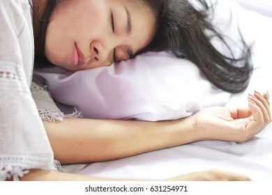 beautiful young Asian woman sleeping in bed