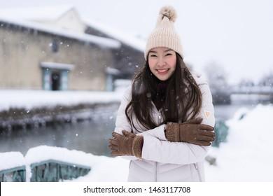Schöne junge Asiatin lächelt und freut sich über die Reise zum Otaru Kanal Hokkaido Japan in der Schnee- und Wintersaison