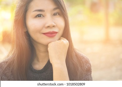 beautiful young Asian woman smiling at the camera with summer or spring nature background