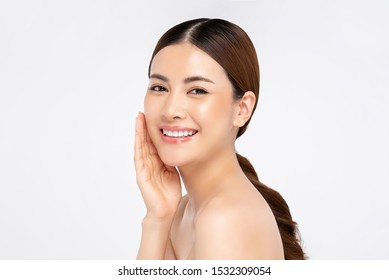 Beautiful young Asian woman smiling with hand touching face isolated on white background for beauty and skin care concepts