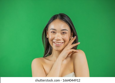 Beautiful young asian woman smiling and looking at camera isolated on green background