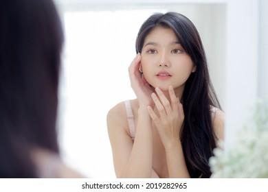 Schöne junge asiatische Frau lächelnd Blick auf den Spiegel der Kontrolle Gesicht mit Hautpflege und Kosmetik für Verjüngung und Hygiene, Schönheitsmädchen glücklich sauber Gesichtscreme oder Lotion und für Gesundheit.
