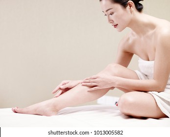beautiful young asian woman with soft skin wrapped in white towel sitting on bed applying body lotion.