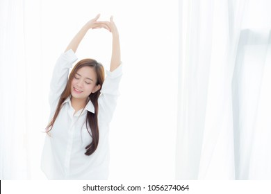 Beautiful young asian woman stretch and relax standing in bed after wake up morning at bedroom, new day and resting for wellness, lifestyle concept.