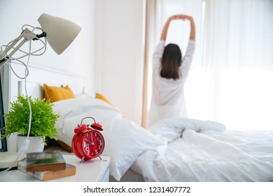 Beautiful young asian woman stretch and relax in bed after wake up morning at bedroom, back view, new day and resting for wellness, lifestyle concept.