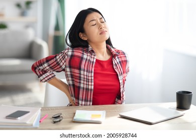 Beautiful Young Asian Woman Suffering From Backache While Sitting At Desk In Home Office, Tired Korean Freelancer Lady Having Acute Lower Back Pain After Long Time Working With Laptop Computer