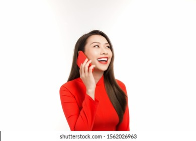 Beautiful young Asian woman talking on phone with someone while wearing red Ao Dai. Isolated on white background