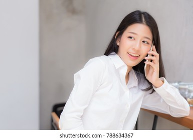 Beautiful young asian woman talking phone and smile in the coffee shop, businesswoman sitting in cafe free time, freelancer female calling telephone, communication concept.