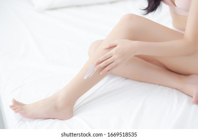 Beautiful young asian woman touch skin leg smooth with cream and lotion for hydration and smooth, girl applying body care and cosmetic for soft, beauty perfect with wellness, health and care.