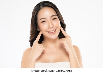 Beautiful young Asian woman touching soft cheek and smile with clean and fresh skin. Happiness and cheerful with, isolated on white background, Beauty and Cosmetics Concept,