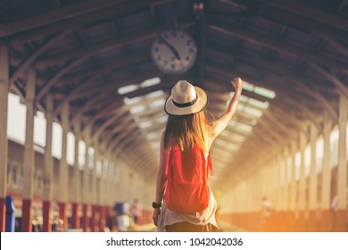 Beautiful young asian woman traveler looking clock over head with red bag ,Waiting for train at train station, Travel and vacation concept.