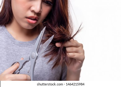 Beautiful young asian woman trimming or cutting her split ends of hair ends. Attractive beautiful young lady get problems of her hair. Gorgeous girl get damaged hair. She get upset, unhappy. isolated