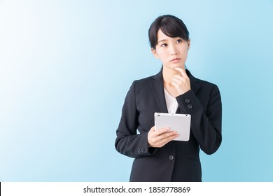 Beautiful young asian woman using tablet computer, think