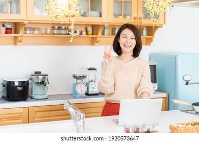 Beautiful young asian woman using laptop,kitchen