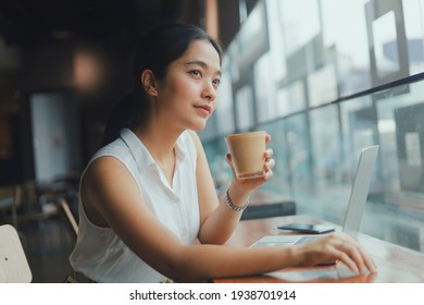 Beautiful young Asian woman using laptop while drinking coffee in cafe  ,Young business woman working in cafe.