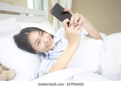 Beautiful young asian woman using smartphone on the bed, 20s year old.