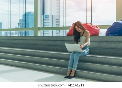 Beautiful young asian woman is using a laptop and smiling while sitting on stairs