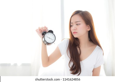 Beautiful young asian woman wake up in morning annoyed alarm clock holding hand, girl standing hurry wake late with appointment with curtain background on bedroom, lifestyle concept.