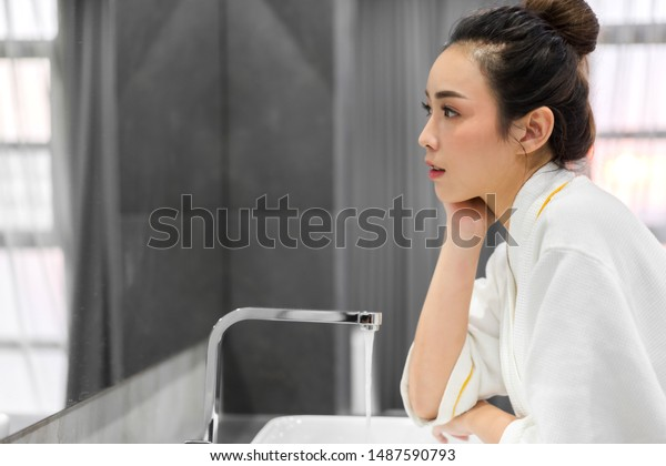 Beautiful young asian woman washing clean face with water and smiling in front of the mirror in the bathroom.beauty and spa.perfect fresh skin