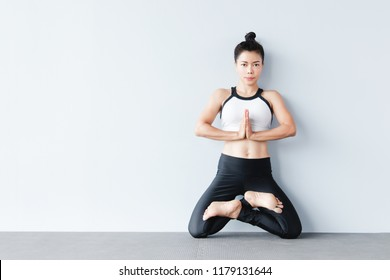 Beautiful young asian woman wearing sportswear practicing yoga in studio,natural light.Concept : yoga poses for beginner.Standing on knees in lotus pose variation. (Padmasana)