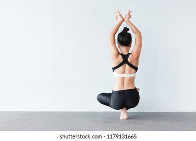 Beautiful young asian woman wearing sportswear practicing yoga in studio,natural light.Concept : yoga poses for beginner.Half Lotus Toe Balance variation. Padangustha Padma Utkatasana.