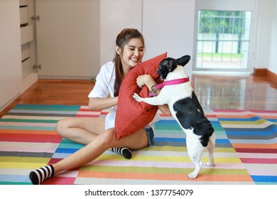 beautiful young asian woman wearing white shirt and holding red pillow who sitting and playing with her cute dog with happy and smiling face in living room. (lifestyle concept)