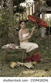 Beautiful young asian woman wearing Thai traditional dress sitting on wooden bench holding red umbrella in the garden with wooden old house background