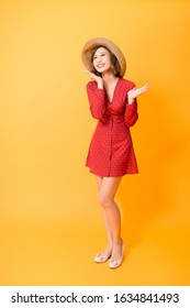 Beautiful Young asian woman wearing a straw hats and red dress over orange background