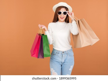 Beautiful young Asian woman wearing a white silk blouse hat and jeans, holding a shopping bag, smiling with a good mood, Shopping cheerful in Holiday at shop in market Center. With a brown background.