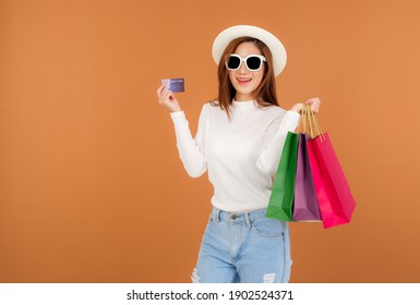 Beautiful young Asian woman wearing white silk blouse and jeans, holding a shopping bag, Wear glasses holding credit card, smile good mood, Shopping in Holiday at shop in market. brown background.