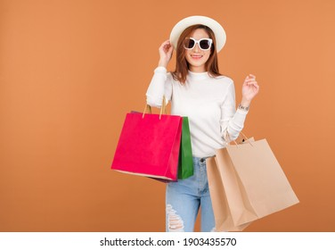 Beautiful young Asian woman wearing white silk blouse , holding a shopping bag, Wear sunglasses holding credit card, smile good mood, Shopping in Holiday at shop in market. brown background.