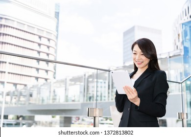 Beautiful young asian woman who see a tablet computer