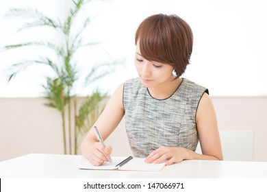 Beautiful young asian woman who fills out a notebook