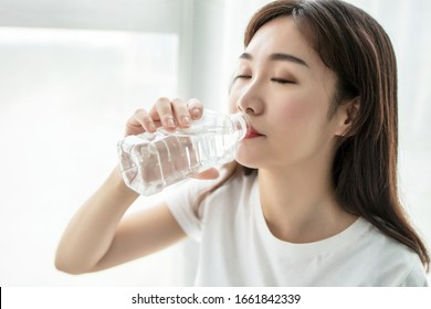 Beautiful young asian woman who drinks water