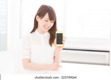 Beautiful young asian woman who shows the screen of the smart phone