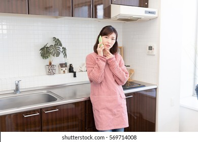 Beautiful young asian woman who talks on the telephone in a kitchen