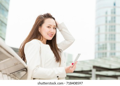 Beautiful young asian woman who sees a smart phone