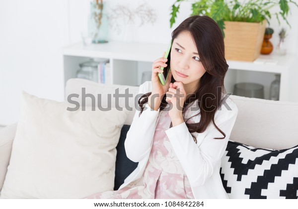 Beautiful young asian woman who talks on the telephone, think,