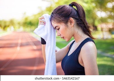 Beautiful young Asian woman wiping off her sweat after her morning exercise at a running track on a brtight sunny morning, woman healthy lifestyle