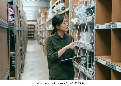 beautiful young asian woman worker of clothes factory doing stock taking in warehouse. girl employee counting products in stockroom. elegant lady staff in storehouse holding clipboard and pen working