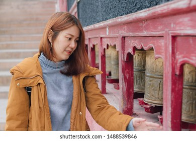 Beautiful young asian woman in yellow jacket rotating praying wheels for religious reason at Thiksey monastery in ladakh, northern india.