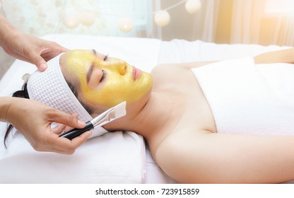 Beautiful young Asian women having high quality authentic pure gold facial mask  , lying on massage table in spa salon