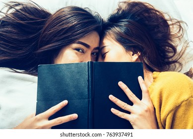 Beautiful young asian women LGBT lesbian happy couple kiss and smiling while lying together in bed under book at home. LGBT funny women after wake up. LGBT lesbian couple together indoors concept.