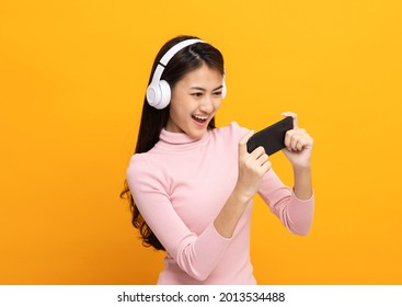 Beautiful young asian women play mobile game and put on wireless headphone standing on isolated yellow background. Playing game on smartphone winning victory moment. Very enjoy and fun relax time