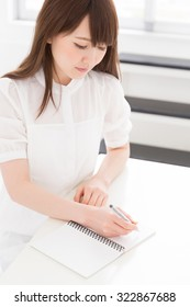 Beautiful young asian women is taking notes and think